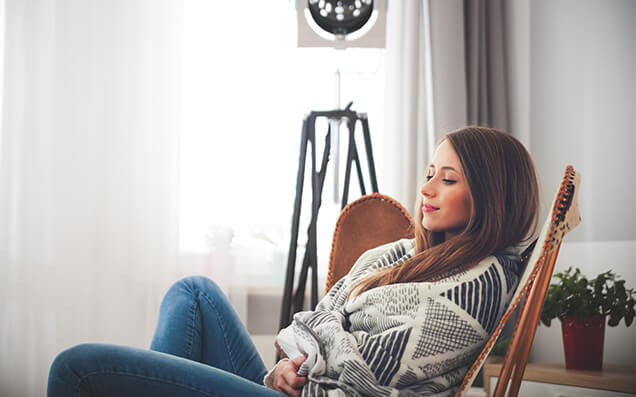 Woman Relaxing in Chair with Heating On